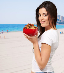 Healthy Woman Holding Bowl Of Cornflakes At Beach