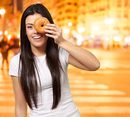 portrait of young woman looking through a donut at city by night