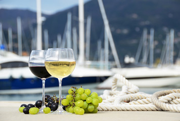 Pair of wineglasses against yacht pier