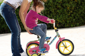 Bambina in bicicletta in salita si fa aiutare