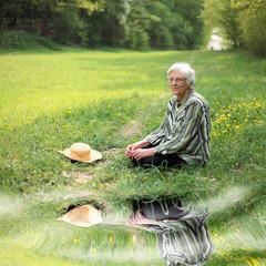 Seniorin im Gras mit Spieglung
