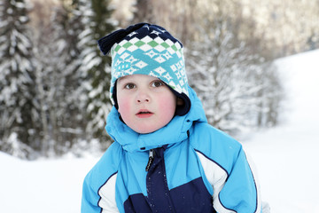Portrait small boy in winter on mountains