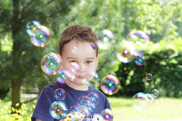 Little boy in the summer park blowing bubbles