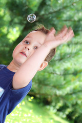 Little boy in the summer park blowing bubbles - trapping bubbles
