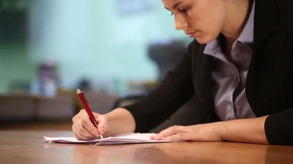 Close-up of young woman with pen and documents
