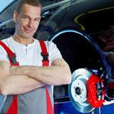 Motor mechanic in a garage has fixed a brake