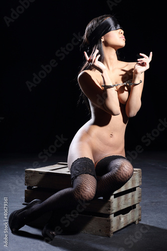 beautiful nude woman with a silk blindfold and handcuff