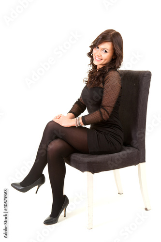 beautiful young woman sitting on chair, full length