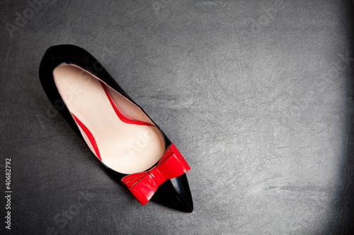 Patent-leather shoe on black leather background