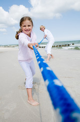 Tug-of-war - girl with mother playing on the beach