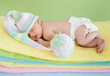 newborn baby girl weared cap sleeping on colourful towels