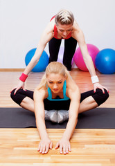 Two girls stretching in club