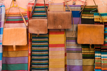 Leather bags and shawls on market in Morocco