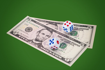 Money with dice on green background.