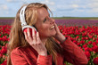 Dutch blond girl with headphones  in field with tulips