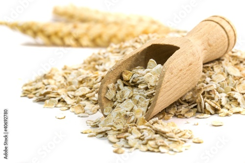 Aluminium Granen Oatmeal flakes with wooden scoop on white background