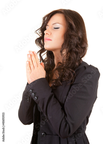 praying young woman with folded hands, white background