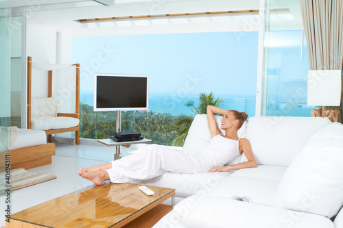 Woman relaxing in spacious bright living-room