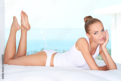 Beautiful woman lying on white bed