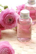 Pink ranunculus flowers and massage lotion, on woven mat