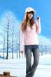 Beautiful winter girl in a hat posing in winter park