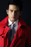 young handsome man in red coat on black background
