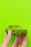 Hand Holding Eco car icon isolate on green background