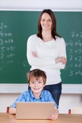 lehrerin und grundschüler mit laptop