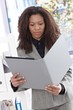 Ethnic businesswoman looking at folder