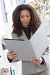 Ethnic businesswoman looking at folder