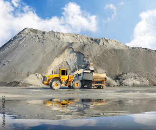 Big excavator and truck in mine.