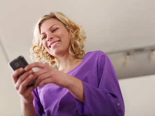 Happy young woman typing text message on mobile phone