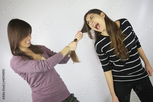 Girl pulling the hair to another girl that shouts