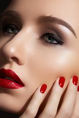 Fashion model with red lips make-up, bright nail polish