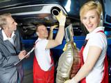 Motor mechanics and apprentice repair exhaust system of a car
