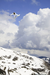 Snowboarder jumping high cloudy sky