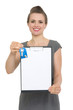 Happy female realtor holding blank clipboard and keys isolated