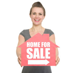 Portrait of smiling realtor showing home for sale sign isolated