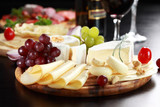 Fototapety Cheese and salami platter with herbs