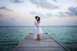 Perfekt happy love couple in white clothes on a jetty (Maldives)