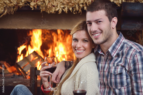 Young romantic couple relaxing in front of fireplace at home