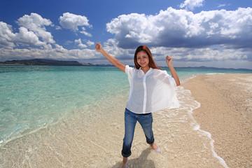 南国の海辺で遊ぶ笑顔の女性