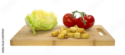 Croutons tomatoes and lettuce on cutting board