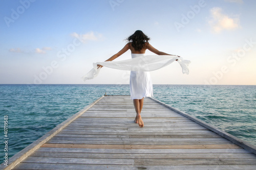 Sexy happy woman in white clothes standing on a jetty (Maldives)