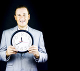 Smiling man in gray suit holding a clock