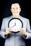 Smiling man in suit, holding clock