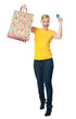 Excited teenager holding shopping bag and card