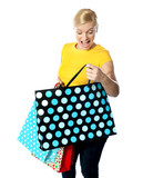 Young girl looking excitedly inside her shopping bag