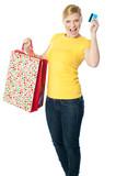 Happy shopaholic girl showing credit card