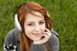 Young fashion girl with headphones sitting at green spring grass